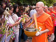 """15 JULY 2011 - PHRA PHUTTHABAT, SARABURI, THAILAND:    People present flowers and candles to monks during the Tak Bat Dok Mai at Wat Phra Phutthabat in Saraburi province of Thailand, Friday, July 15. Wat Phra Phutthabat is Phra Phutthabat, Saraburi, Thailand, is famous for the way it marks the beginning of Vassa, the three-month annual retreat observed by Theravada monks and nuns. The temple is highly revered in Thailand because it houses a footstep of the Buddha. On the first day of Vassa (or Buddhist Lent) people come to the temple to """"make merit"""" and present the monks there with dancing lady ginger flowers, which only bloom in the weeks leading up Vassa. They also present monks with candles and wash their feet. During Vassa, monks and nuns remain inside monasteries and temple grounds, devoting their time to intensive meditation and study. Laypeople support the monastic sangha by bringing food, candles and other offerings to temples. Laypeople also often observe Vassa by giving up something, such as smoking or eating meat. For this reason, westerners sometimes call Vassa the """"Buddhist Lent."""" The tradition of Vassa began during the life of the Buddha. Most of the time, the first Buddhist monks who followed the Buddha did not stay in one place, but walked from village to village to teach. They begged for their food and often slept outdoors, sheltered only by trees. But during India's summer rainy season living as homeless ascetics became difficult. So, groups of monks would find a place to stay together until the rain stopped, forming a temporary community. Wealthy laypeople sometimes sheltered monks on their estates. Eventually a few of these patrons built permanent houses for monks, which amounted to an early form of monastery.  PHOTO BY JACK KURTZ"""