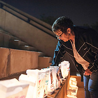 Paula Hill, lights a Luminaria in memory of her mother Fabby Hill at Relay for Life Friday, June 21 at McKinley County Courthouse Square in Gallup. Hill lost her mother to ovarian cancer nine years ago.