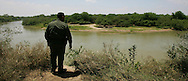 Photo by Alex Jones..US Border Patrol agent J. Garcia looks across the Rio Grande into Mexico from a brushy area west of Hidalgo while on patrol on May 15.