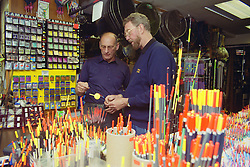 Two men working in fishing tackle shop examining fish hook,