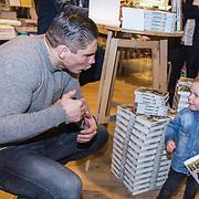 NLD/Amsterdam/20171222 - Signeersessie Rico Verhoeven en Leon Verdonschot, Rico Verhoeven overhandigt een boek aan een klein jongetje