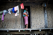 A mother carries her baby in her arm and stands at the porch of a tradtional Reungao ethnic tribe house.  Walls are in wattle and daub. Kontum plateau, Pleiku area, Vietnam, Asia