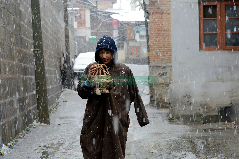 A Kashmir young boy holding Kashmiri traditional firepot to keep himself warm during the snowfall in Srinagar, the summer Capital of Indan controlled Kashir. Kashmir witnessed its first snowfall.