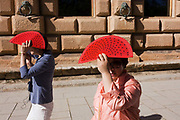 Tourists from Asia walk in the sunshine at Alhambra,  holding matching red fans to shield their faces from strong sunshine. The visitors walk along the outer walls of the renaissance Palacio de Carlos V in the Moorish fortress high above the Andalucian city. Alhambra (in Arabic, Al-Ḥamra) is a palace and fortress complex constructed during the mid 14th century by the Moorish rulers of the Emirate of Granada in Al-Andalus, occupying the top of the hill of the Assabica on the southeastern border of the city of Granada in the Autonomous Community of Andalusia. The Alhambra's Moorish palaces were built for the last Muslim Emirs in Spain and its court, of the Nasrid dynasty.