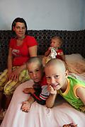 Liliana en 2011 avec ses enfants dans la pièce où elle vit dans la maison de ses beaux-parents. Liliana est mère au foyer et son compagnon est un homme du village qui travaille dans le bâtiment en Allemagne. <br /> <br /> Liliana with her three children in the room where she lived at her in-laws' in Popricani in 2011. Liliana's husband was abroad, working as a builder in Germany.