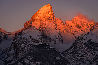 The first light of the last day of 2016 touches Grand Teton while clouds swirl around Mount Owen. This mountain is nothing short of grand. It towers 13,775 feet above sea level, just shy of Wyoming's highest peak. From the moment the Tetons first come into view while driving through the valley, I find it hard to look away. These dramatic, sawtooth-shaped mountains are spectacular any time of the year, but especially so in winter. The summit is flanked on both sides by 2 glaciers.