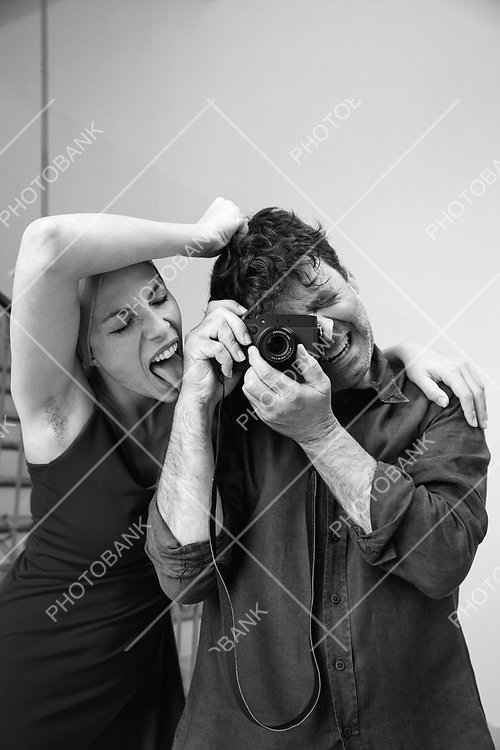 Young attractive woman licks a hairy arm of a photographer. Disgust