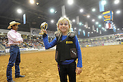 Child Sheep Racing<br /> <br /> Mutton busting is an event held at rodeos similar to bull riding or bronc riding, in which children ride or race sheep<br /> In the event, a sheep is held still, either in a small chute or by an adult handler while a child is placed on top in a riding position. Once the child is seated atop the sheep, the sheep is released and usually starts to run in an attempt to get the child off. Often small prizes or ribbons are given out to the children who can stay on the longest. There are no set rules for mutton busting,<br /> The vast majority of children participating in the event fall off in less than 8 seconds. Age, height and weight restrictions on participants generally prevent injuries to the sheep, and implements such as spurs are banned from use. In most cases, children are required to wear helmets and parents are often asked to sign waivers to protect the rodeo from legal action in that event.<br /> <br /> Photo shows: Lexi Gorman, 7, holds up her mutton busting trophy in the arena at the Tri-State Fair and Rodeo in Amarillo, Texas<br /> ©Exclusivepix