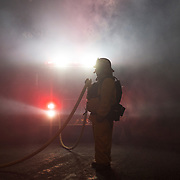 A firefighter holds a hose in the smoke along Cachagua Road while fighting the Carmel Fire in Cachagua, Calif. on Aug. 18, 2020.