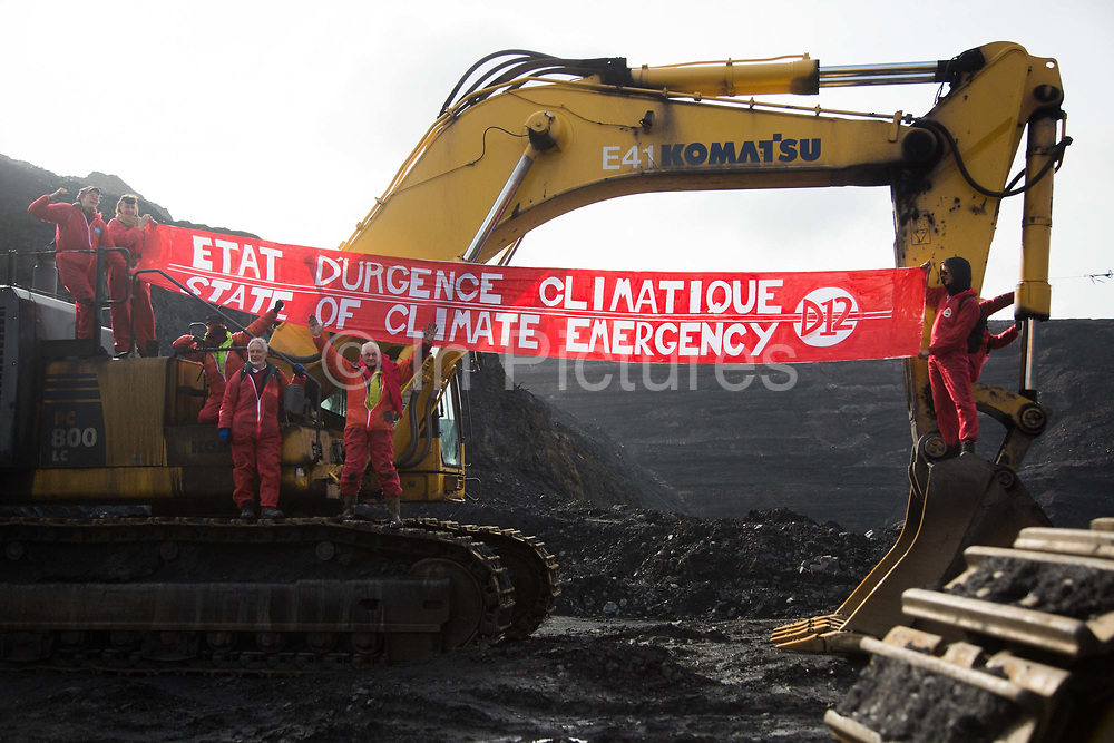 Hundreds of environmental activists stopping the open cast coal mine Ffos-y-Fran near Merthyr Tydfil, Wales from operating May 3rd 2016. Unchallenged by security the activists enter the mine which is not in operation and empty for any other activity and set up banners and form a symbolic red line in the black sand.The activists from Reclaim the Power wants the mine shut down and a moratorium on all future open coal mining in Wales. The group Reclaim the Power had set up camp near by and had over three days prepared the action and up to 300 activists all dressed in red went into the mine in the early morning. The activist were plit in three groups and carried various props signifying the red line in the sand, initially drawn in Paris at the COP21. The mine is one of the largest open cast coal mines in the UK and is run by Miller Argent who have to date extracted 5million tons of coal. The activists entered the mine unchallenged by any security or police and the protest went on peacefully till mid afternoon with no arrests made.  Open coal mining is hugely damaging to the local environment and  contributing to global climate change.