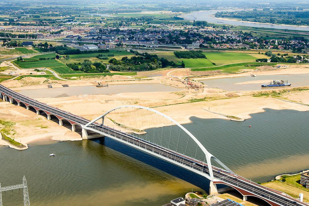 Nederland, Gelderland, Nijmegen, 26-06-2014; de nieuwe stadsbrug van Nijmegen over rivier de Waal, De Oversteek.  Links van de rivier grondwerkzaamheden voor de Dijkteruglegging Lent (Ruimte voor de Rivier).<br /> First bridge the new city bridge of Nijmegen on the river Waal, De Oversteek (The Crossing). To the left of the river groundwork for the Dike relocation of Lent (project Ruimte voor de Rivier: Room for the River).<br /> luchtfoto (toeslag op standaard tarieven);<br /> aerial photo (additional fee required);<br /> copyright foto/photo Siebe Swart.