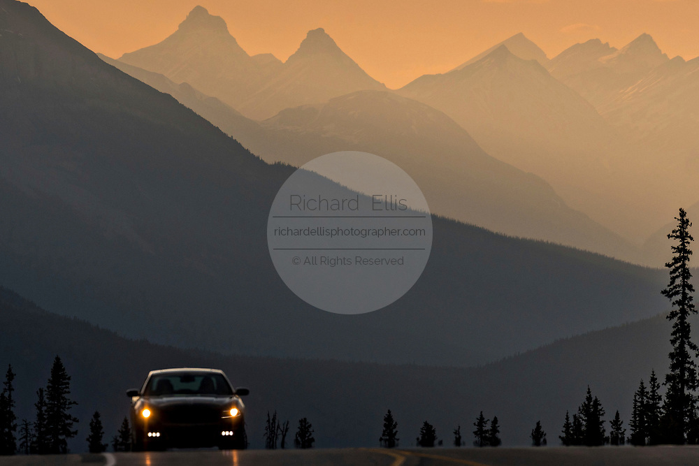 A car travels along the Icefields Parkway as the sunsets over the Canadian Rockies at Jasper National Park in Alberta, Canada.