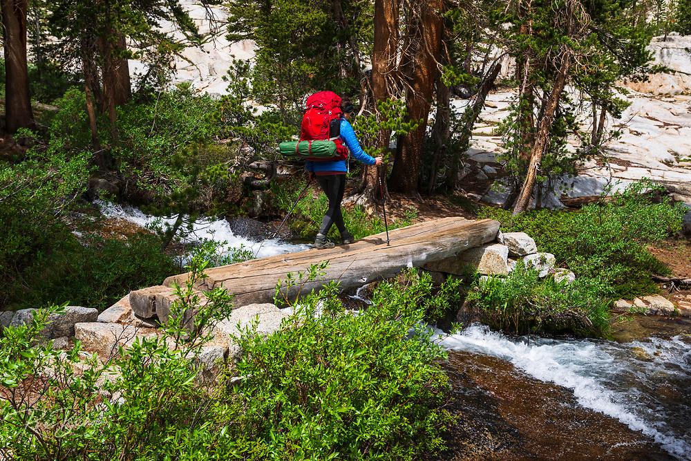 Backpacker crossing Bishop Creek on the Treasure Lakes trail, John Muir Wilderness, Sierra Nevada Mountains, California USA