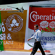 BEIRUT,LEBANON - MAY 2009 : A man passes by a billboard in Hamra street. Beirut. Lebanon. 05/29/2009 ( Photo by Jordi Cami )
