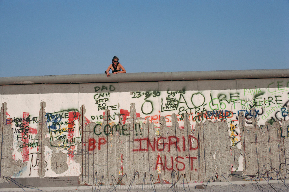 A woman leans over the top of the Berlin Wall. Germany. In the spring of 1990, the Berlin Wall was a tourist destination before it was completely dismantled. People used hammers and chisels to take pieces for souvenirs. Germany.