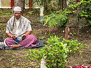 06 JULY 2016 - BANGKOK, THAILAND: After Eid services, men pray at a grave in the cemetery at Bang Luang Mosque in the Thonburi section of Bangkok. It is traditional for people to clean the graves of family members after Eid. Eid al-Fitr is also called Feast of Breaking the Fast, the Sugar Feast, Bayram (Bajram), the Sweet Festival or Hari Raya Puasa and the Lesser Eid. It is an important Muslim religious holiday that marks the end of Ramadan, the Islamic holy month of fasting. Muslims are not allowed to fast on Eid. The holiday celebrates the conclusion of the 29 or 30 days of dawn-to-sunset fasting Muslims do during the month of Ramadan. Islam is the second largest religion in Thailand. Government sources say about 5% of Thais are Muslim, many in the Muslim community say the number is closer to 10%.        PHOTO BY JACK KURTZ