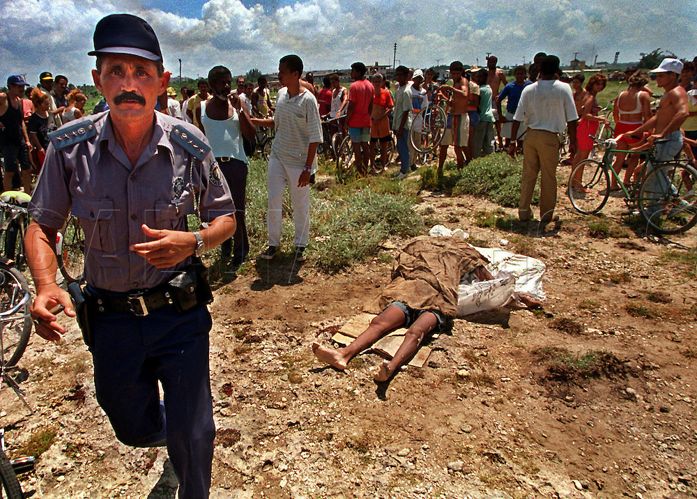 8/21/1994-Al Diaz/Miami Herald--A Cuban police officer disperses a crowd of onlookers viewing the corpse of a Cuban rafter washed ashore and dragged to this location at Cojimar. In 1994 Cuban balseros turned the tiny fishing village into a major point of embarkation for thousands seeking a better life.