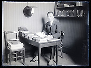 writer or librarian with books sitting on a table France circa 1920s