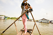 13 MARCH 2006 - CHAU DOC, AN GIANG, VIETNAM: A rows a small boat through a floating village on the Mekong River near Chau Doc, Vietnam in the Mekong delta. The Mekong is the lifeblood of southern Vietnam. It is the country's rice bowl and has enabled Vietnam to become the second leading rice exporting country in the world (after Thailand). The Mekong delta also carries commercial and passenger traffic throughout the region.  Photo by Jack Kurtz