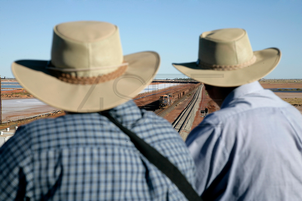 Tourists on a road ramp watching long trains passing carrying iron ore in Port Hedland.