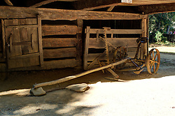 an old hay cutting implement that was horse drawn is shown in the blacksmith shop at Cades Cove Historic Area Visitors Center in Blount County Tennessee.  Cades Cove is within the Great Smoky Mountains National Park