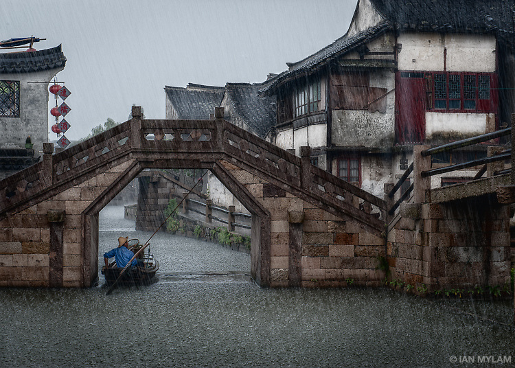 A boatman takes shelter from the torrential rain in Xitang, Zhejiang, China