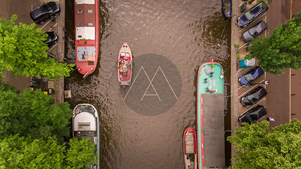 Aerial view of a small boat driving in the canal of Amsterdam, The Netherlands.