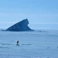 Inuit youngsters ride their bikes on the frozen Arctic Ocean near Pond Inlet on Baffin Island, Nunavut, Canada.  Behind them is an iceberg that has run aground after drifting from Greenland.