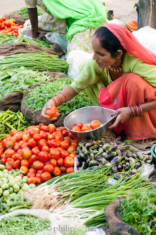 A woman at a fresh vegetable stall at a market in Jaisalmer, Rajasthan, India