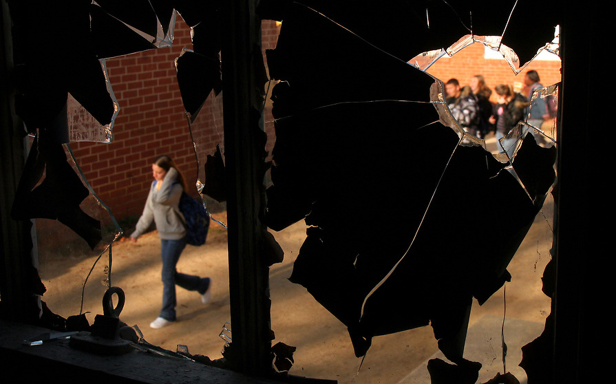 J.V. Martin Junior High School students pass by broken windows of the auditorium on their way to class.