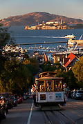 Riding the historic Powell-Hyde cable car, Alcatraz in background, San Francisco, CA