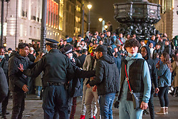 Licensed to London News Pictures. 10/10/2020. London, UK. Revellers dancing with blaring sound system at Piccadilly Circus, central London; while the police intervenes in a scuffle.  After the 10pm curfew early closing of pubs and bars. Photo credit: Marcin Nowak/LNP