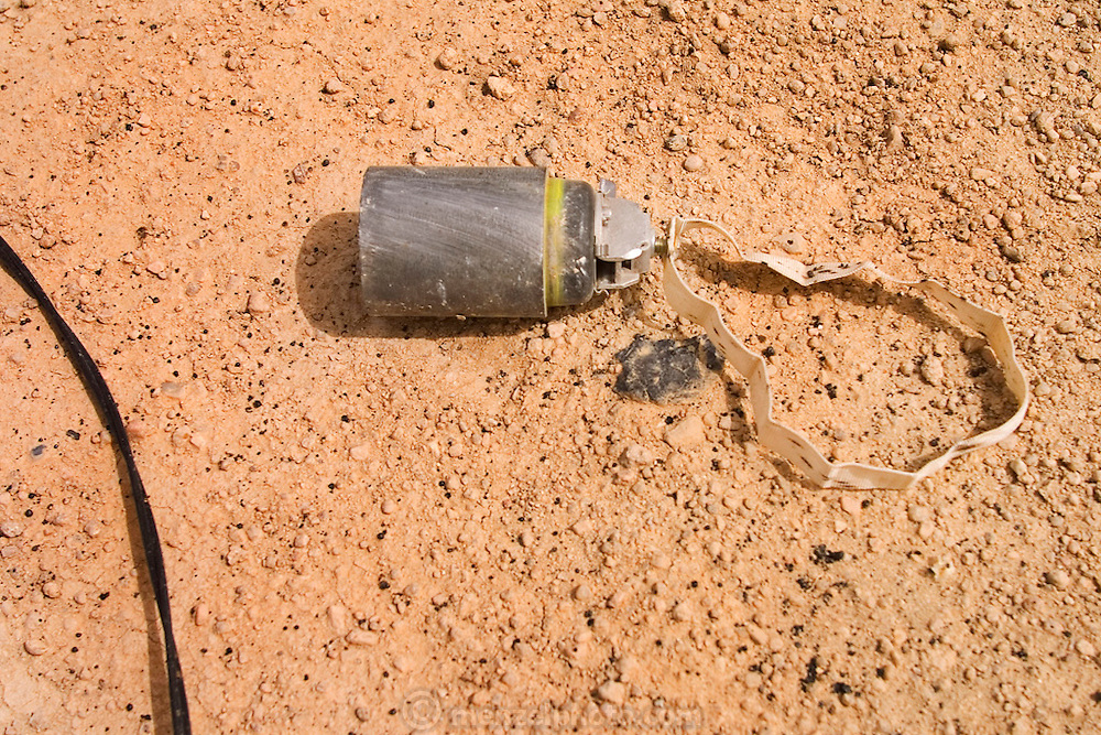 Stray cluster bomb in Rumaila oilfield, Southern Iraq. Unexploded cluster bombs litter the area around the burning oil wells of Rumaila. The wells were set on fire with explosives by retreating Iraqi troops when the US and UK invasion began. The Rumaila field is one of Iraq's biggest oil fields with five billion barrels in reserve. Rumaila is also spelled Rumeilah.