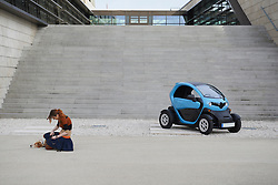 Young woman with dog and electric car in front of staircase, Munich, Bavaria, Germany
