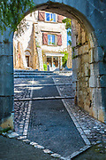 """Entrance gate to Saint Paul de Vence in France.<br /> -----<br /> Saint-Paul or Saint-Paul-de-Vence is a commune in the Alpes-Maritimes department in southeastern France. One of the oldest medieval towns on the French Riviera, it is well known for its modern and contemporary art museums and galleries such as Fondation Maeght which is located nearby. It was probably between the 10th and 12th century that a settlement formed around the ancient church of Saint Michel du Puy to the south, and near the castle on the highest part of the hill. In the Middle Ages, the region was administered by the Counts of Provence. In the 13th century, Count Charles II granted more privileges to St. Paul, including the right to hold a weekly market. At the beginning of 14th century, St. Paul acquired more autonomy and became a prosperous city of merchants and nobility. In 1388, the County of Nice broke off from Provence to reattach itself with the states belonging to the Count of Savoy. These new circumstances gave St. Paul a strategic position: the city becomes a border stronghold for five centuries. St. Paul went through its first fortification campaign in the second half of 14th century: the north gate of the city, called """"Porte de Vence,"""" dates back to the medieval wall. At the time of the wars of Italy, Provence was invaded twice by the troops of Charles V. Considering the low side of the border of Provence and the obsolescence of the medieval fortifications in Saint-Paul, Fran�ois 1st decided in 1538 to build the new city walls, able to withstand the power of the artillery. This fortified wall, built between 1543 and 1547, is preserved in its entirety. On its northern and southern fronts four solid bastions protect both the city gates. In the 17th century, Saint-Paul experienced a religious period through the influence of Antoine Godeau, Bishop of Vence. The church was elevated to college, and was expanded and embellished. St. Paul also saw an urban revival thanks to the families o"""