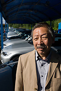 Japanese entrepreneur, Tetsuro Hama with cars for sale at his north London car dealership business. Hama is the owner of So plus a north London car dealership. He arrived from Japan in 1973, looking for business opportunities before starting a hotel in a Bayswater backstreet. He then went into the restaurant industry, soon earning the respect of employees and customers for affordable and tasty sushi. From the chapter entitled 'The Price of Happiness' and from the book 'Risk Wise: Nine Everyday Adventures' by Polly Morland (Allianz, The School of Life, Profile Books, 2014).