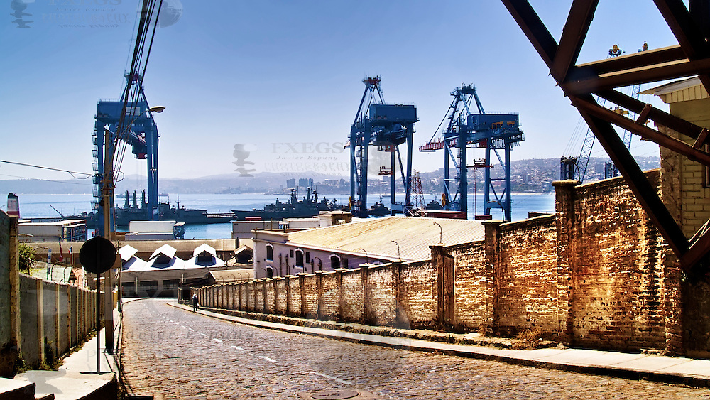A long street with a wall and the sea with the docks on background