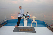 The writer, essayist and philosopher Alain de Botton leans against the wheel of a traditional dhoni boat in the Indian Ocean. De Botton is in the Maldives researching his book 'The Pleasures and Sorrows of Work' about the world of Work, published in April 2009. Here he accompanies a fishing boat crew who use hand and line methods to land yellow fin tuna for export to the EU and in particular, Sainsbury's supermarket. Barefoot on the roof of the wheelhouse and with the top of his pen in mouth, he looks thoughfully into the distance to think of more great ideas for his best-selling book. Alain de Botton (born Zurich, 1969) now lives in London. His best-selling books refer both to his own experiences and ideas- and those of artists, philosophers and thinkers. It's a style of writing that has been termed a 'philosophy of everyday life.'