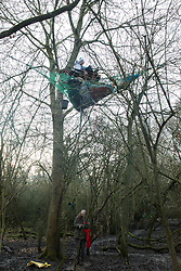 Harefield, UK. 20 January, 2020. An activist on the ground communicates with activists living in the trees at the Colne Valley wildlife protection camp. Extinction Rebellion, Stop HS2 and Save the Colne Valley had reoccupied the camp two days before as part of an ongoing attempt to protect ancient woodland threatened by the HS2 high-speed rail link after a small group of Stop HS2 activists had been evicted by bailiffs over the course of the previous two weeks. 108 ancient woodlands are set to be destroyed by the high-speed rail link.