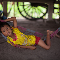 A young Cambodian boy rests in a hammock under his house.
