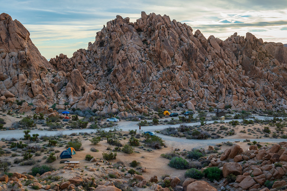 Cars are parked outside tents at Indian Cove campground in Joshua Tree National Park in California.