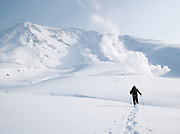 A hiker trekking in the snow towards a volcanic steam vent in Daisetsuzan National Park, Hokkaid?, Japan