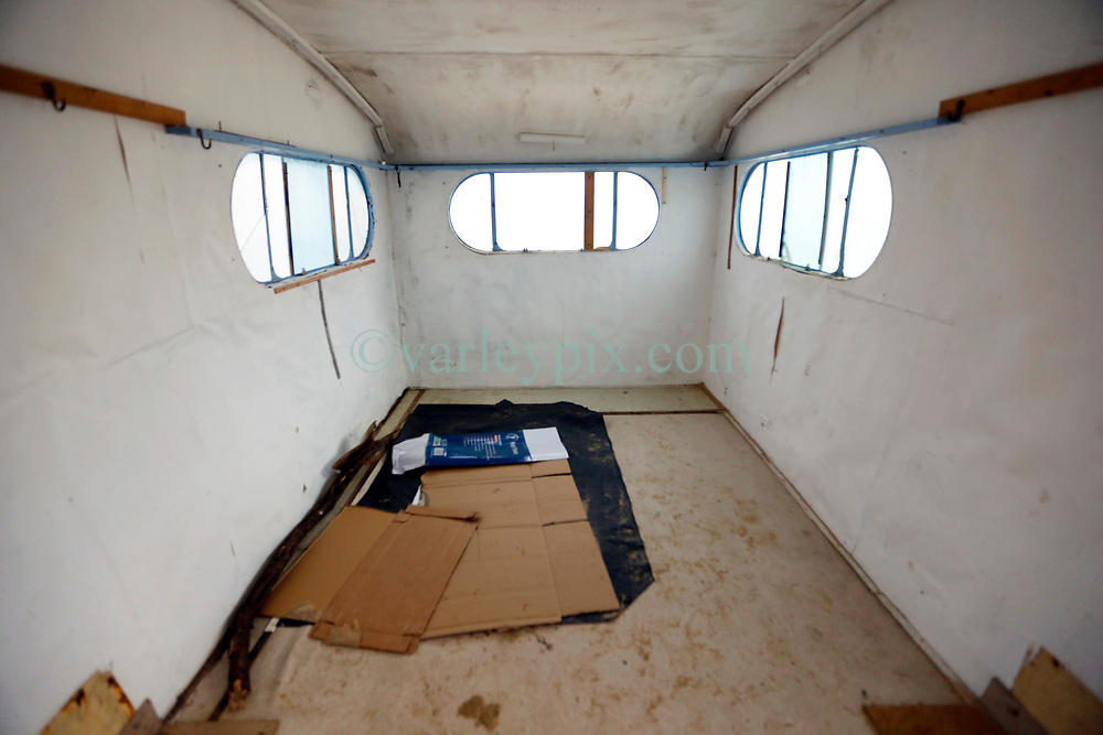 30 June 2020. South of Calais, France.<br /> Smuggler's Paradise. Interior of a seemingly deserted old caravan hidden in the sand dunes of a beach south of Calais where local police claim migrants often attempt the treacherous crossing to Great Britain. The caravan appears to have been recently used with cardboard laid on the ground for bedding and passport photos discovered on the sandy floor. The location is reasonably remote and backs onto farmland. A gravel access road makes this a prime location for ruthless criminal gangs to drop migrants paying as much as €5,000 for a ticket on an inflatable dinghy with a small outboard motor and less for surfboards and inflatable kayaks. Local police claim it is from here and other beaches in the region that migrants often set out to make desperate and dangerous attempts to cross one of the busiest shipping lanes in the world. Migrants are crossing the English Channel (La Manche) by boat, kayak, surf board and even inflatable paddling pools as numbers seeking asylum in the UK continue to rise. <br /> Photo©; Charlie Varley/varleypix.com