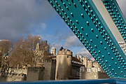 The Tower of London in the distance with the steel rivets from one of Tower Bridge's steel suspension anchor girders, on 14th December 2017, in the City of London, England.