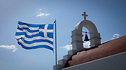 Greek flag blowing in the wind over one of the many churches in Mykonos Town, Greece