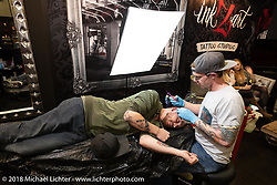 Tattooing studio setup in Intermot Customed's hall 10 during the Intermot International Motorcycle Fair. Cologne, Germany. Saturday October 6, 2018. Photography ©2018 Michael Lichter.