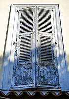 Two closed grey shutters with peeling paint over a window on a pale white wall. Rust is seen on the shutter's hinges.