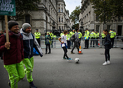 © Licensed to London News Pictures. 07/10/2019. London, UK. Extinction Rebellion protestors play football in a closed street outside Downing Street in Westminster. Activists will converge on Westminster blockading roads in the area for at least two weeks calling on government departments to 'Tell the Truth' about what they are doing to tackle the Emergency. Photo credit: Ben Cawthra/LNP