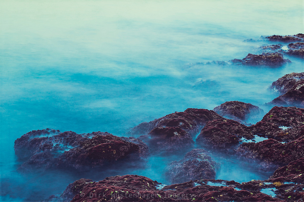 Long exposure shot of waves washing over dark rocks on the shores of the Atlantic Ocean