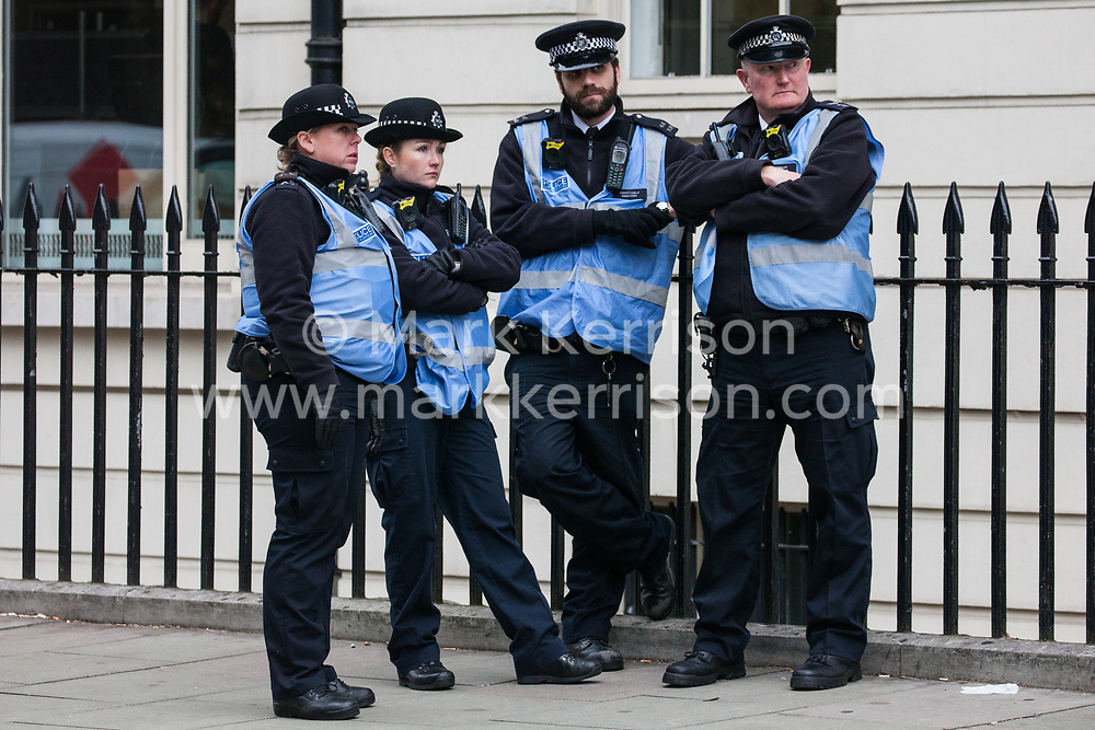 London, UK. 30th October, 2018. Police officers observe members and supporters of the Independent Workers of Great Britain (IWGB) trade union at a rally following a march with precarious workers from the offices of Transport for London to the University of London via the Court of Appeal in support of Uber drivers who are seeking employment rights. The Court of Appeal will today hear an appeal by Uber against a ruling that its drivers are employees rather than self-employed workers.